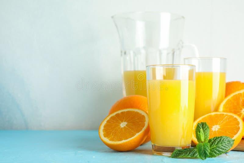 Skład z świeżym sokiem pomarańczowym w glassware, nowego i drewnianego juicer na koloru stole przeciw białemu tłu, zdjęcie royalty free