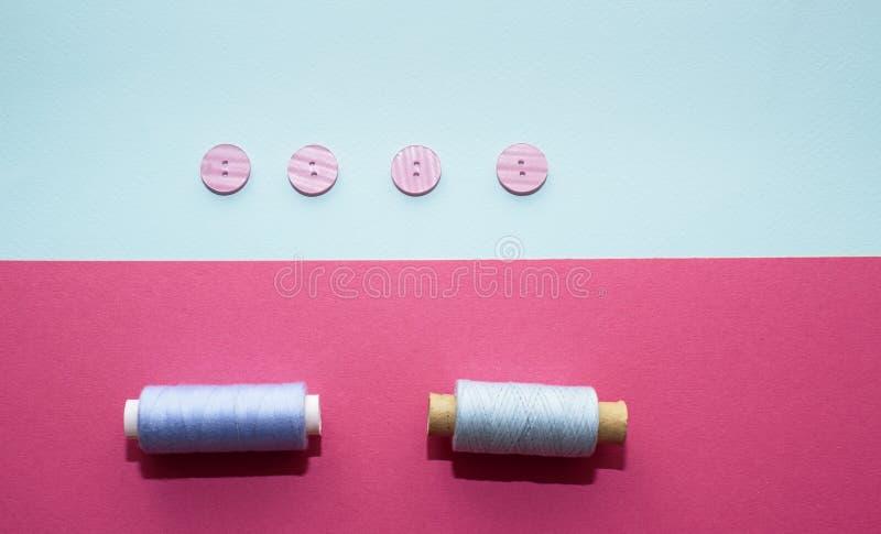 Skład z błękitnymi niciami i szwalnymi akcesoriami na różowym tle zdjęcia stock