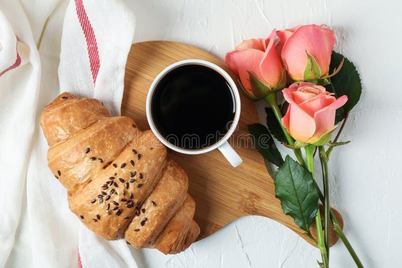 Skład z croissant, filiżanka kawy, różami i kuchennym ręcznikiem na białym tle, obrazy stock