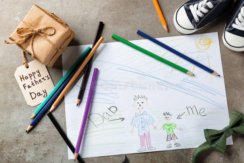 Skład z dzieckiem, s rysunkiem i prezenta pudełkiem na stole « Szczęśliwy ojciec, s dnia świętowanie « fotografia royalty free