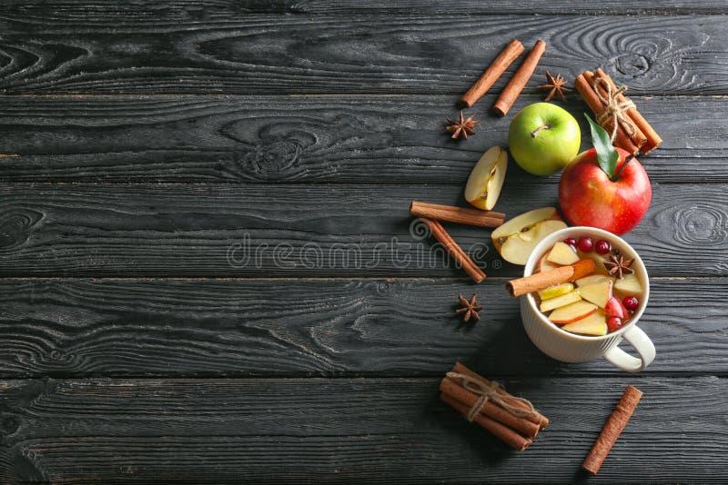 Skład z filiżanką świezi jabłko wodni i cynamonowi kije na drewnianym tle obraz royalty free