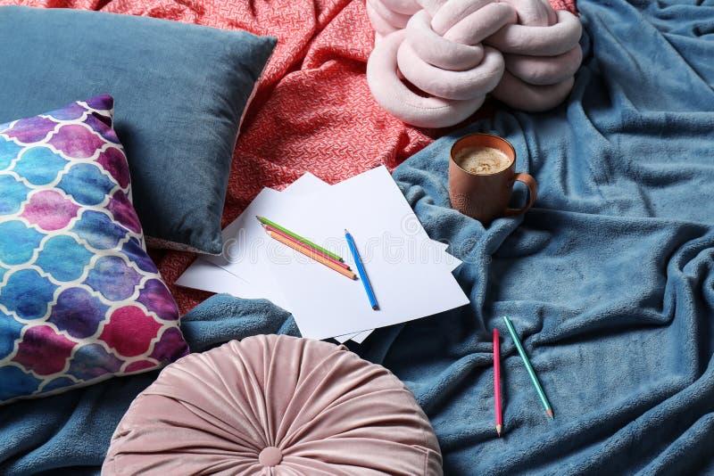 SkÅ'ad z filiżankÄ… kawy, ołówkami i plamiona na łóżku zdjęcie stock