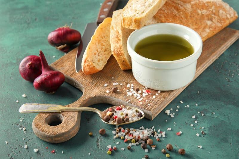 Skład z oliwą z oliwek, pikantność i chlebem na kolorze, textured tło fotografia royalty free