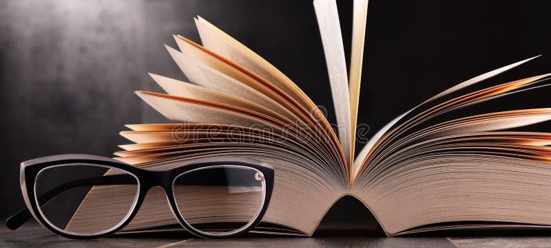 Skład z otwartą książką i szkłami na stole zdjęcia stock