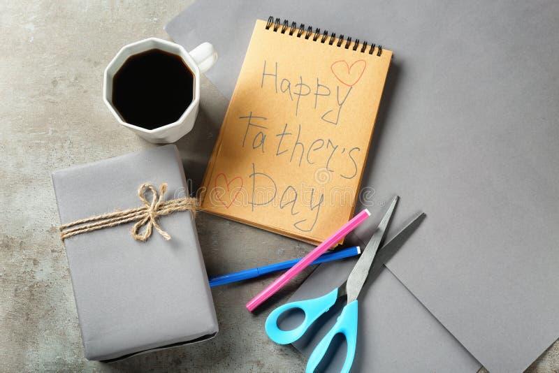 Skład z pudełkiem, filiżanka kawy i notatnikiem na popielatym tle prezenta, Szcz??liwy ojca dnia ?wi?towanie obraz royalty free