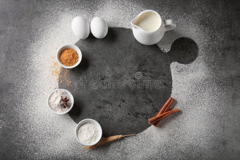 Skład z rozrzuconą mąką i składnikami na popielatym tle obrazy stock