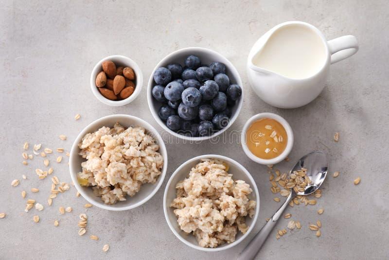 Skład z smakowitym oatmeal, świeżymi jagodami, mlekiem i miodem na stole, zdjęcia stock