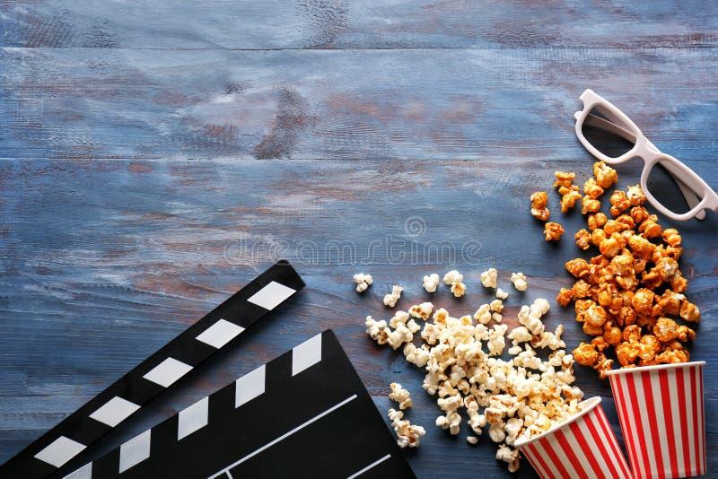 Skład z smakowitym popkornem i clapperboard na drewnianym tle zdjęcia royalty free