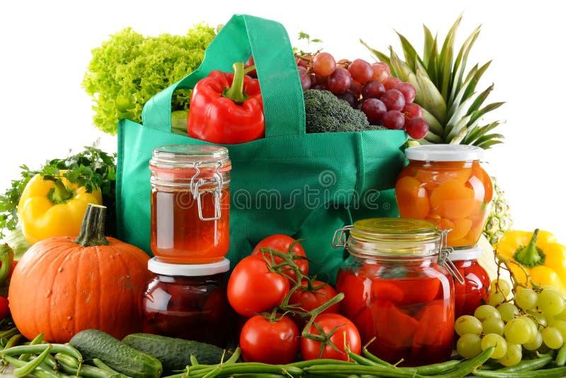 Skład z torba na zakupy i żywnością organiczną nad bielem fotografia stock