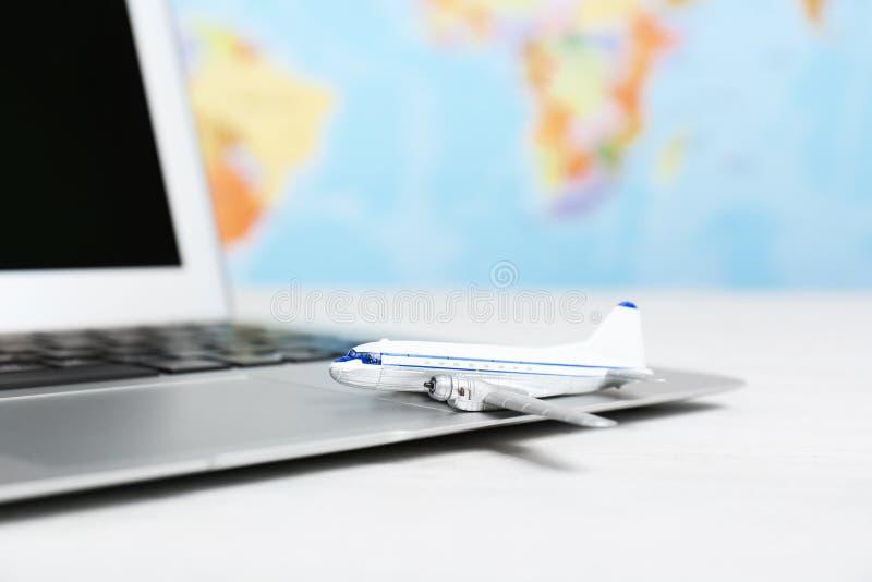 Skład z zabawka laptopem na stole przeciw mapie i samolotem Podróż obrazy stock