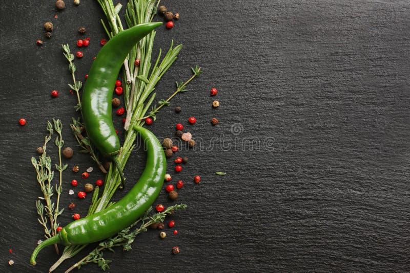 Skład z zielonym chili, pikantność i świeżymi ziele na czarnym textured tle, fotografia royalty free