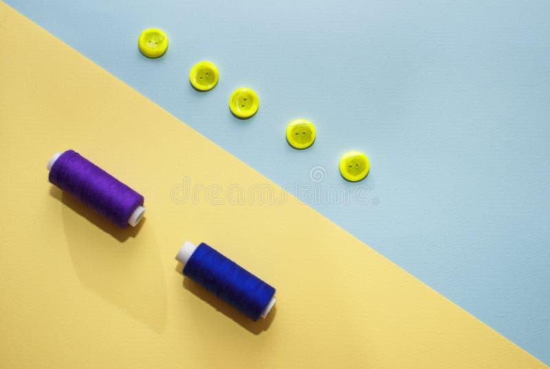 Skład z zmrokiem błękitne nici i szwalni akcesoria na żółtym tle - obraz royalty free