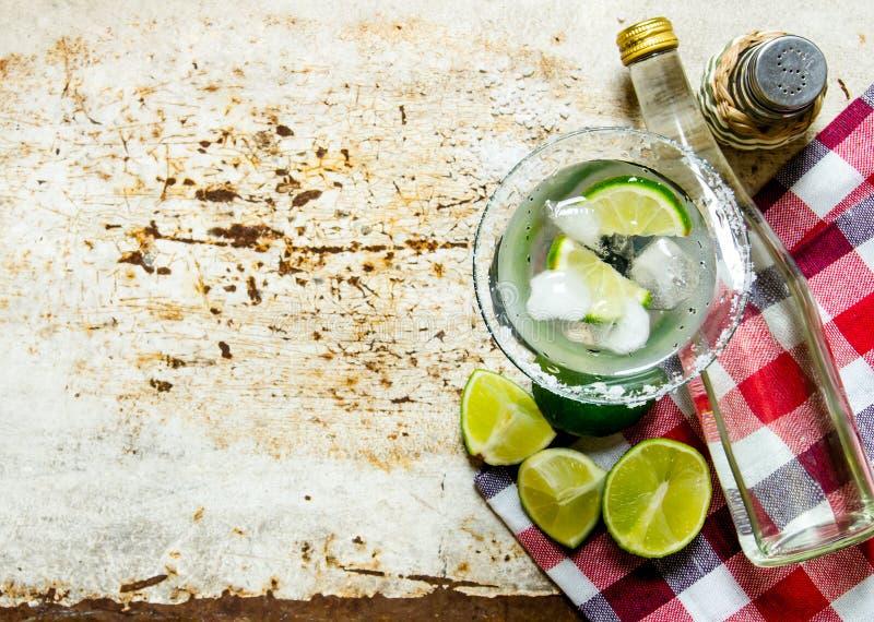 Składnika koktajl wapno, lód, tequila, sól i ajerkoniak na starym tle -, Uwalnia przestrzeń dla teksta zdjęcia stock