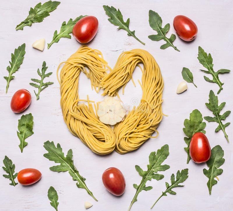 Składnika makaronu surowy serce wykładał z czereśniowych pomidorów arugula czosnku tła drewnianym nieociosanym zakończeniem w gór obraz stock