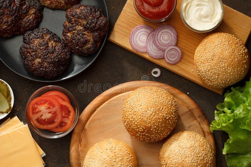 Składniki dla domowej roboty hamburgerów na stole obrazy stock