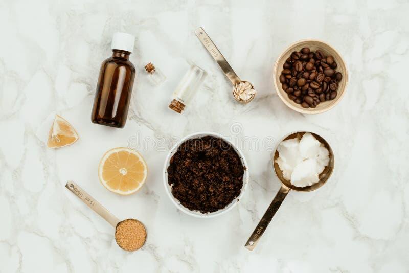 Składniki dla domowej roboty skóry pętaczki na marmurze: zmielony kawy, kokosowego i istotnego olej, zdjęcia stock