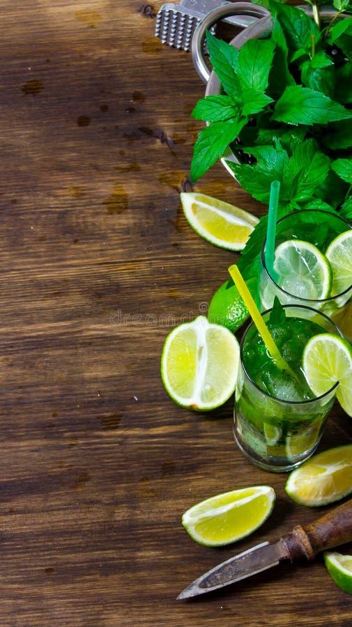 Składniki dla koktajli/lów wapno, rum, nowi liście, kostki lodu na drewnianym stole zdjęcia stock