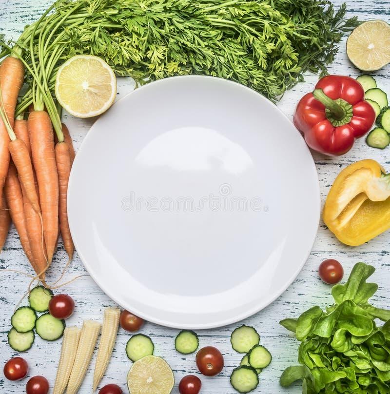 Składniki dla kulinarnych sałatkowych czereśniowych pomidorów, sałaty, pieprzy, pikantność i oleju kłaść out wokoło bielu talerza obrazy stock