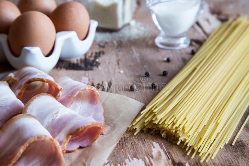 Składniki dla makaronu Carbonara z bekonem, serem, śmietanką i yolk na drewnianym stole, Narządzanie spaghetti alla carbonara obrazy royalty free