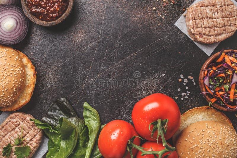 Składniki dla mięsnych hamburgerów na ciemnym tle, odgórny widok, kopii przestrzeń obrazy royalty free