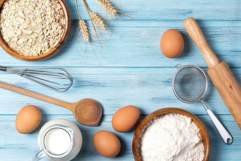 Składniki dla piec, mleka, jajek, pszenicznej mąki, owsów i kitchenware na błękitnym drewnianym tle, odgórny widok zdjęcie royalty free