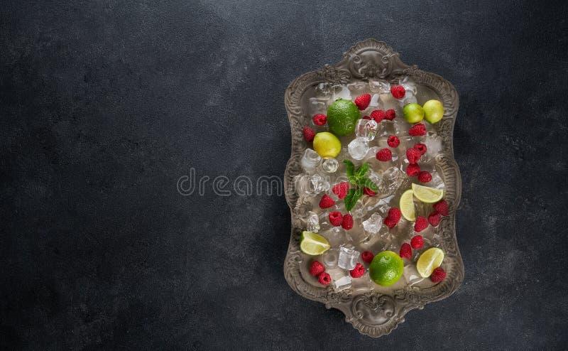 Składniki dla robić lemoniad kostkom lodu, malinka, wapno cytryna i mennica, słuzyć na starej tacy nad ciemnym wieśniakiem fotografia royalty free