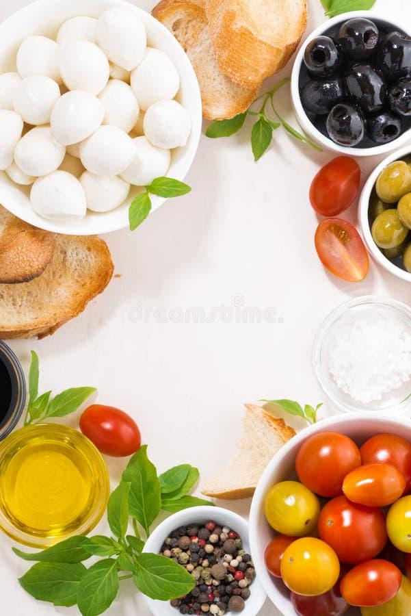 Składniki dla sałatki z mozzarellą na bielu stole, pionowo obraz stock