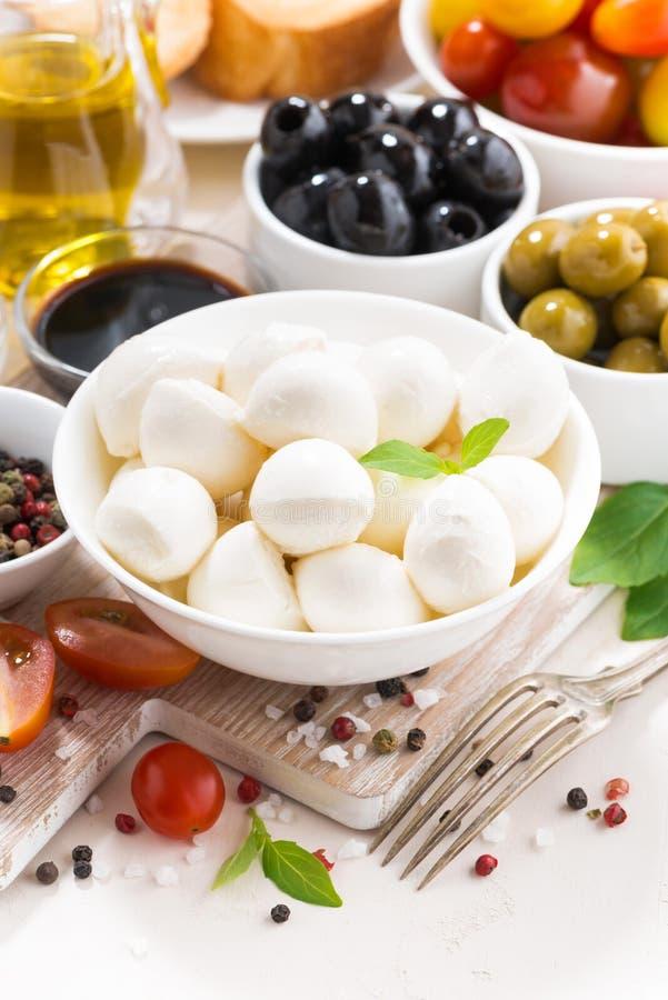Składniki dla sałatki z mozzarellą na bielu stole, pionowo zdjęcia royalty free