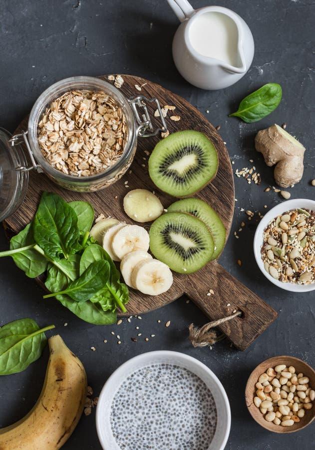 Składniki dla zdrowego śniadania - chia pudding, oatmeal, banan, kiwi, szpinak, kokosowy mleko na ciemnym tle, odgórny widok zdjęcia royalty free