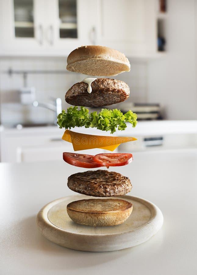 Składniki Hamburgera latające w kuchni obraz stock