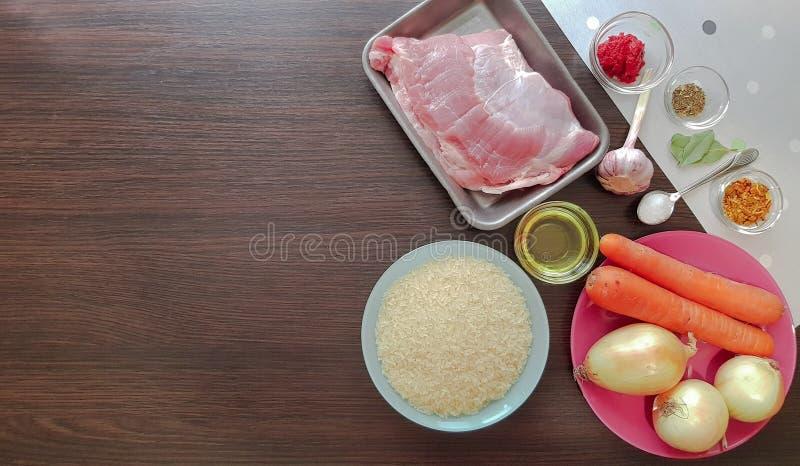 Składniki pilafu do gotowania z wieprzowiną. Surowa polędwica wieprzowa, ryż basmati, cebula, nasiona kminku, przyprawa, pomid fotografia royalty free