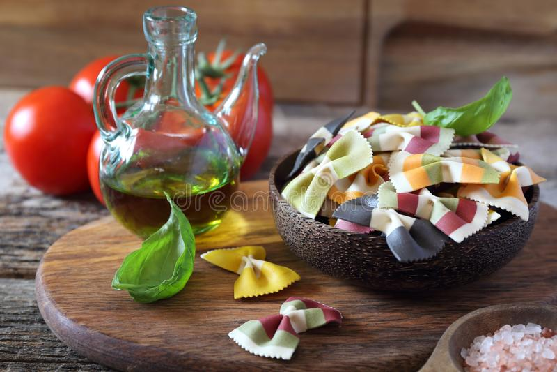 Składniki Włoska kuchnia: surowy farfalle makaron, wiązka dojrzali pomidory, basil i oliwa z oliwek, fotografia royalty free