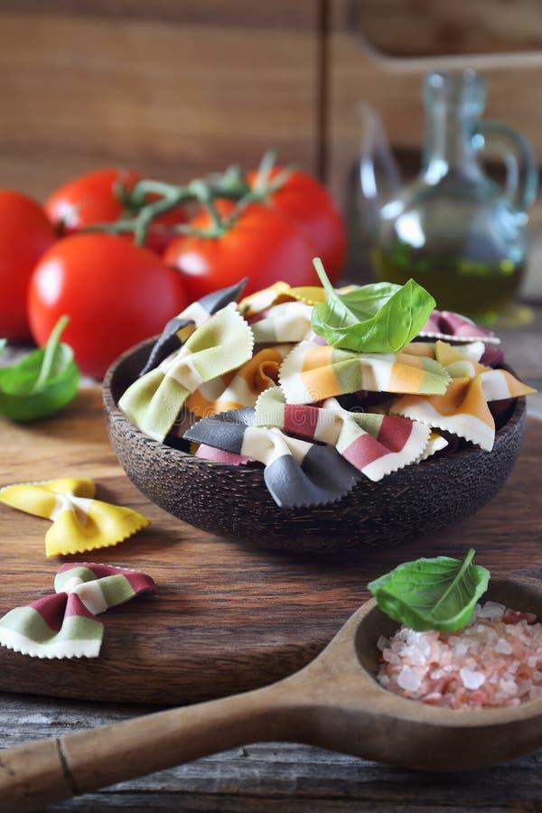 Składniki Włoska kuchnia: surowy farfalle makaron, wiązka dojrzali pomidory, basil i oliwa z oliwek, fotografia stock