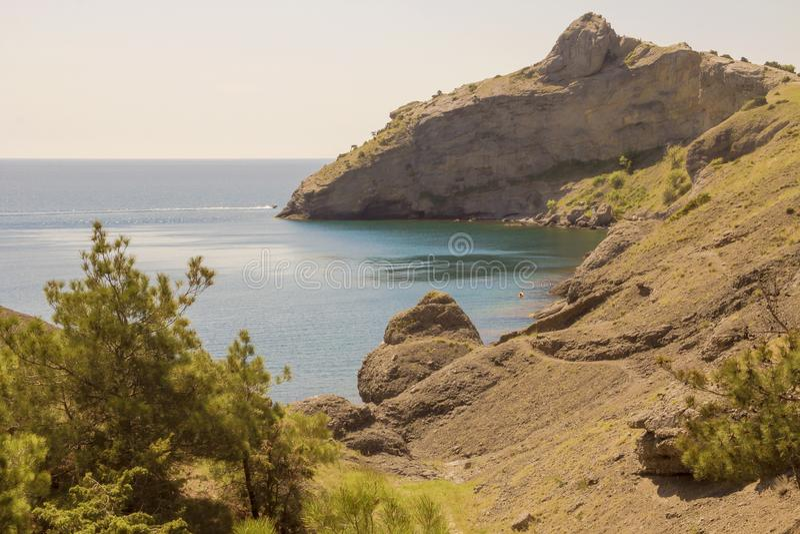 Skłon góra i przylądek, zakrywający z rzadkimi iglastymi roślinami i ziele, graniczy morze zatoki zdjęcia stock