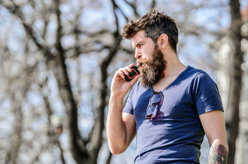 Sk?ggig brutal man som r?ker den elektroniska cigaretten Man som r?ker E-cigaretten vaping apparat f?r hipstermanh?ll V?rd- s?ker royaltyfri foto