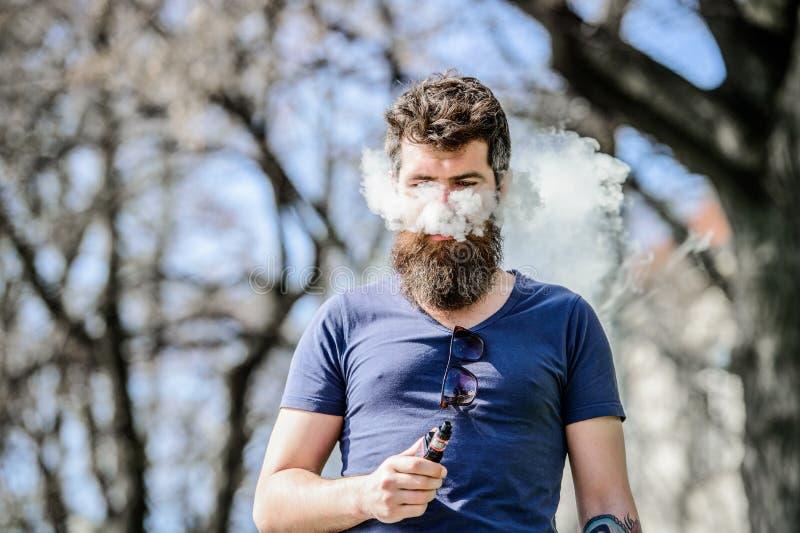 Sk?ggig brutal man som r?ker den elektroniska cigaretten Mogen hipster med sk?gget Man som r?ker E-cigaretten hipstermanh?ll royaltyfria bilder