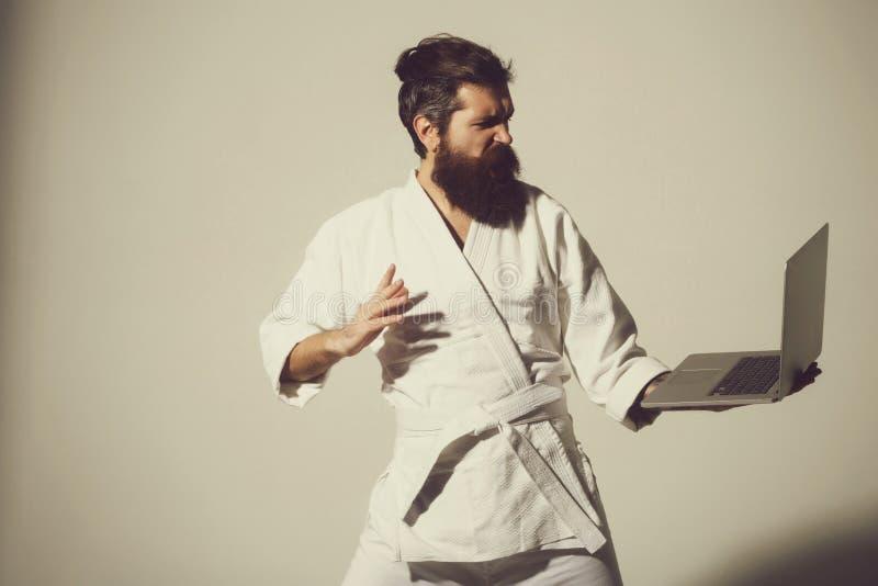 Sk?ggig ilsken karateman i kimono med b?rbara datorn arkivfoto