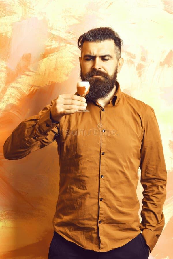 Sk?ggig man, l?ngt sk?gg Brutal caucasian allvarlig hipster med mustaschen i h?llande alkoholiserat r?tt skott f?r brun skjorta p arkivbilder