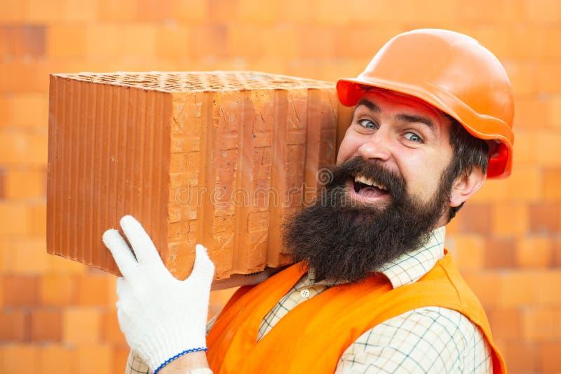 Sk?ggig manarbetare, sk?gg, byggnadshj?lm, h?rd hatt Byggmästare i hård hatt och handskar St?ende av den lyckliga arbetaren _ royaltyfri fotografi