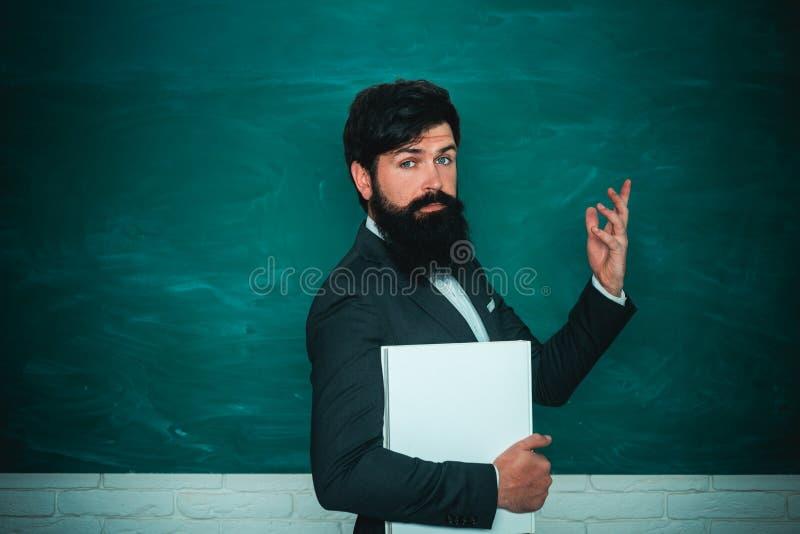 Sk?ggig professor p? skolakursen p? skrivbord i klassrum Dra tillbaka till skolan och lycklig tid Utrymme f?r h?gstadiumbegreppsk fotografering för bildbyråer