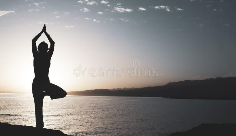 Sk?nhetflickan p? stranden i yoga poserar, kopplar av konturn royaltyfri bild