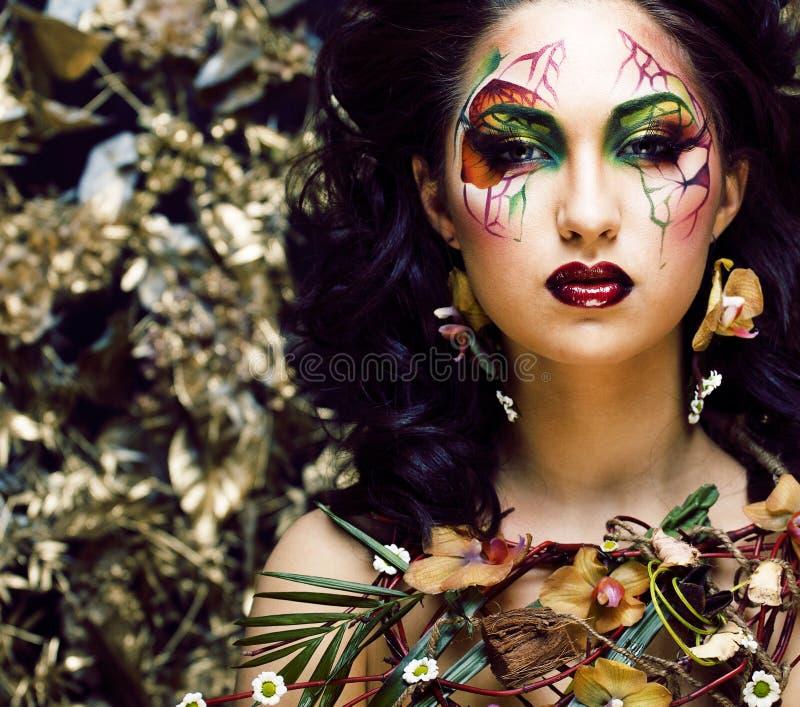 Sk?nhetkvinnan med framsidakonst och smycken fr?n blommaorkid?r st?nger sig upp, blom- modellbakgrund f?r id?rik makeup fotografering för bildbyråer