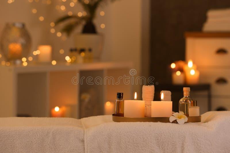 Sk?nhetsmedel och brinnande stearinljus p? massagetabellen i brunnsortsalong arkivfoton