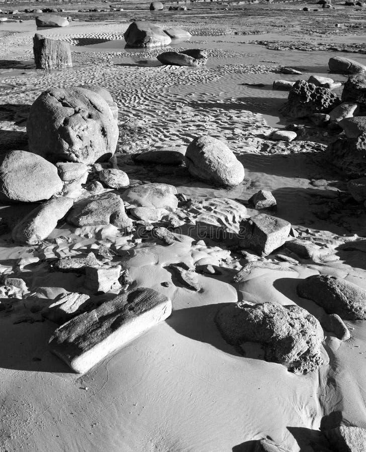 Skały i głazy na plażowym czarny i biały wizerunku obraz stock