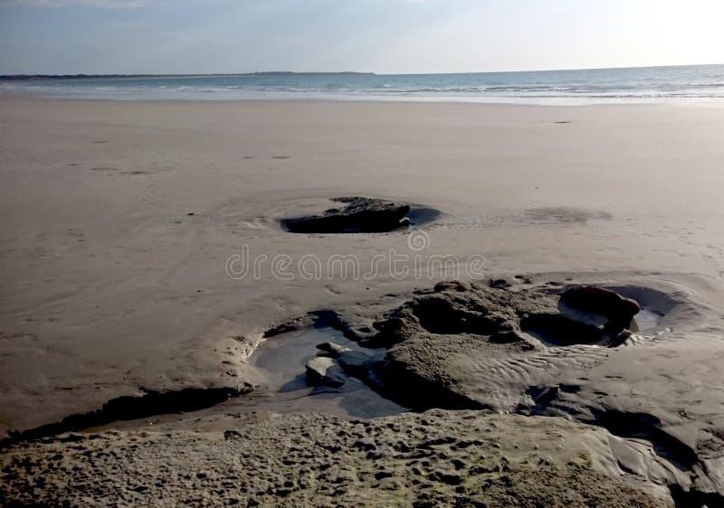 Skały i kałuże na piasku przy kablem Wyrzucać na brzeg obrazy royalty free
