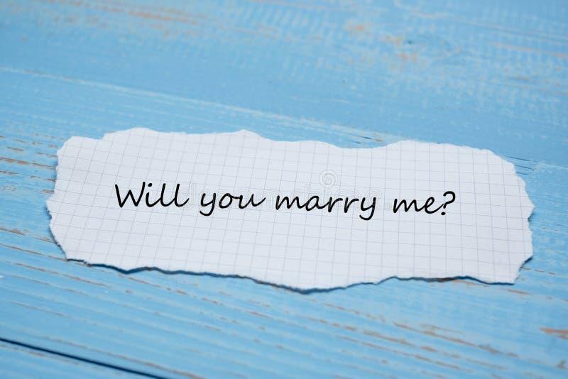 SKA DU ATT GIFTA SIG MIG? ord på pappers- anmärkning på blå trätabellbakgrund Gifta sig, romantisk och lycklig Valentine' s dag arkivbilder