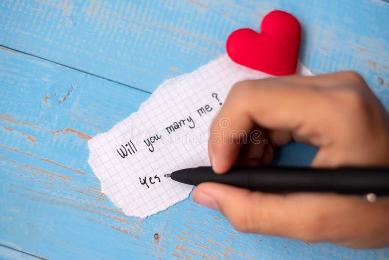 SKA DU ATT GIFTA SIG MIG? ord på pappers- anmärkning på blå trätabellbakgrund Gifta sig, romantisk och lycklig Valentine' s dag royaltyfria foton