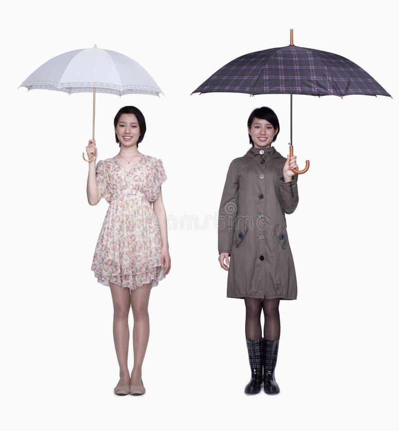 Skaczą i spadają, uśmiechnięte młode kobiety z parasolem, studio strzał zdjęcia stock