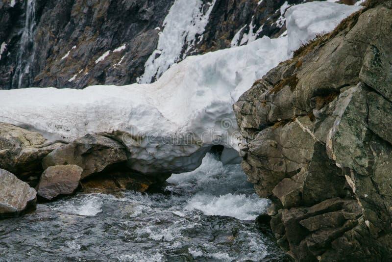 Skacze w górach, śnieżny stapianie z rzeka przepływem zdjęcia stock
