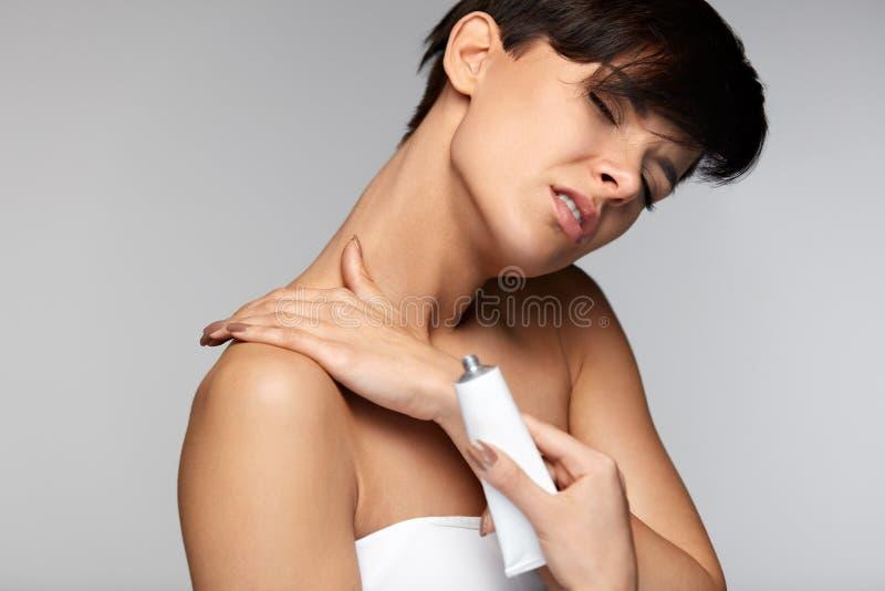 Skadabehandling Den härliga kvinnan med halsen smärtar applicerar kräm royaltyfria foton